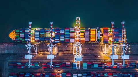 Container ship at deep sea port at night, Business import export logistic and transportation of International by container cargo ship in the open sea, Aerial view time lapse.