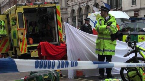London, United Kingdom (UK) - 05 09 2012: Police guard crime scene where a dead man lies on a stretcher