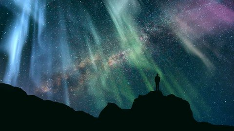 The man standing on a mountain against a starry sky with a northern light