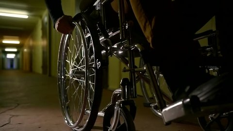 Close up shot of a disabled man on a wheelchair in abandoned scary hospital.