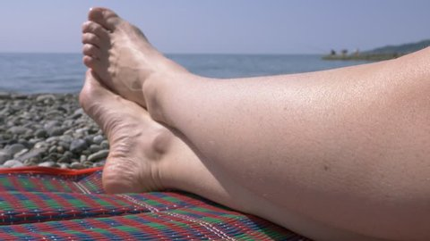 not shaved pubic hair on the thighs of women, natural beauty. girl with unshaven legs and a bikini area in a swimsuit on the beach, 4k