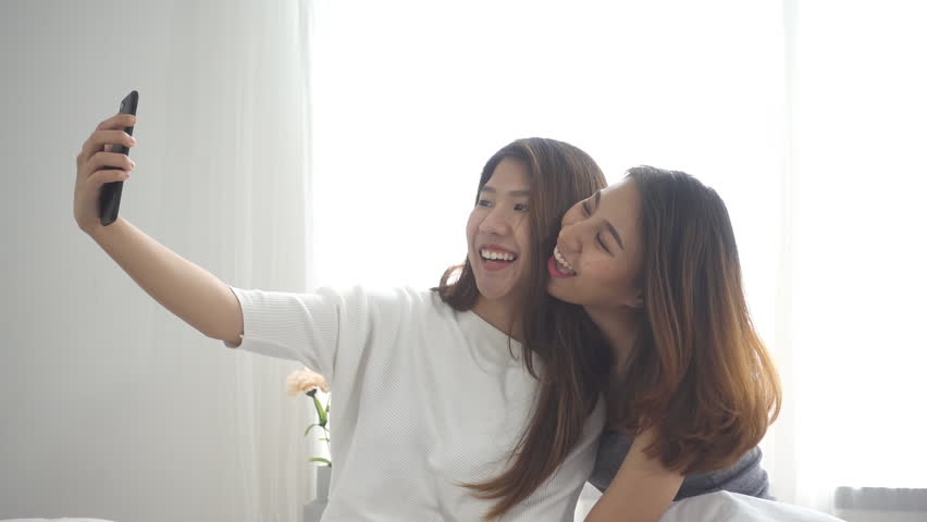 Slow motion - Beautiful young asian women LGBT lesbian happy couple sitting  on bed hug and using phone taking selfie together bedroom at home.