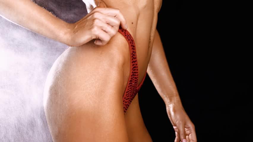 Slim Female Bodybuilder Posing In Red Bikini on a black background 4K footage Isolated