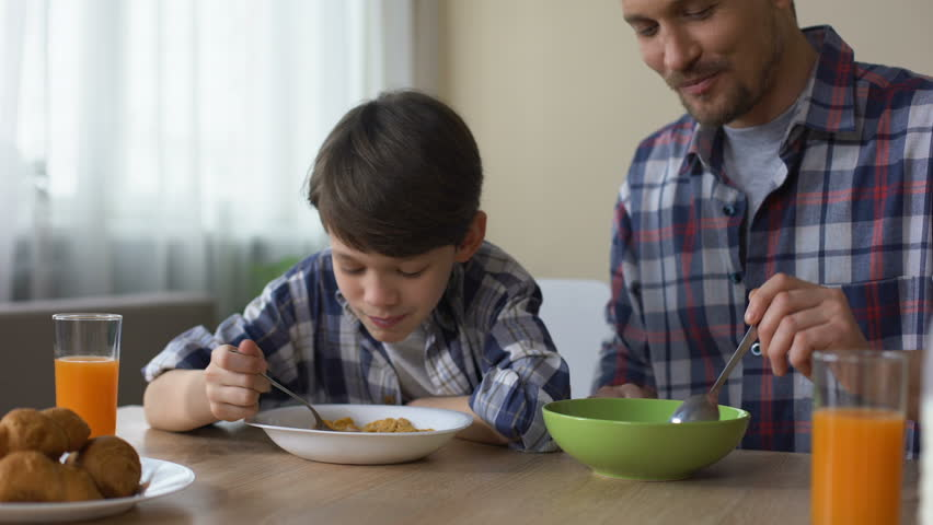 Pleased son and father eating tasty cornflakes at breakfast, morning tradition