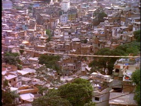 BRAZIL, 1998, Slums of Rio de Janeiro, favelas, on hillside, tilt up to luxury towers