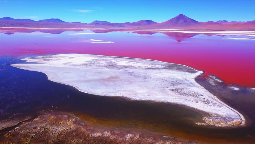 Laguna Colorada with vivid orange water and salt islets aerial shot. Altiplano, Bolivia | Shutterstock HD Video #1010466023