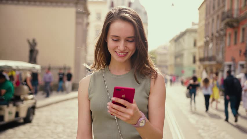 Attractive young woman in a bright sunlight uses phone walk in the city center strokes her hair looks around smile happy summer internet business outside technology eye spring mobile slow motion | Shutterstock HD Video #1010479433