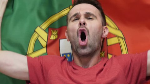 Portuguese Fan celebrates holding the flag of Portugal in Slow Motion