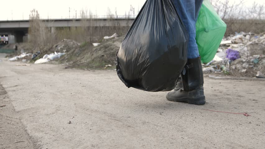 Close-up back view of male legs in dirty boots walking at garbage dump site. Man holding trash bags full of plastic for recycling walking along city landfill site. Steadicam shot