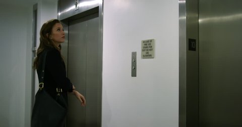 Medium shot, side view, smartly dressed business woman waits for elevator, steps inside and pushes button for floor. Hand-held, slow motion 4K 60fps.