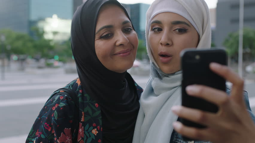 Portrait of young muslim women posing daughter kisses mother on cheek taking selfie photo using smartphone camera technology in urban city background real people series