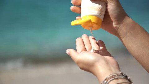 Girl squeezing sun protect cream. Young woman holds a tube of sunblock product, squeezing it out on palm of her hand. Shot at Thassos island, Greece.