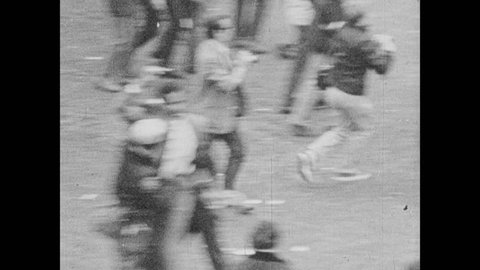 1960s: UNITED STATES: crowds gather during protest. Police move crowds back during protest. Police arrest protestors. Police man with baton
