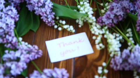 Beautiful spring flowers lily of the valley and lilac flowers on woodward wooden background.