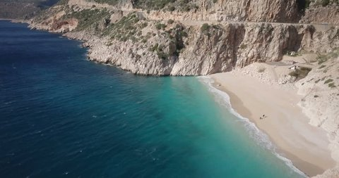Forward aerial drone video passing famous Kaputas Beach and cars on cliffside highway above Mediterranean Sea near Kas, Turkey. 4k at 23.97fps