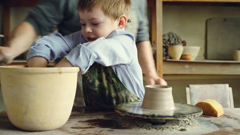 Cute child is learning pottery in traditional workshop together with senior grandfather. He is wetting hands, forming piece of clay on throwing wheel.