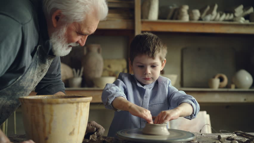 Little boy pottery learner is creating clayware on throwing-wheel while his experienced grandgather is talking to him and helping him. Making ceramics and family concept.