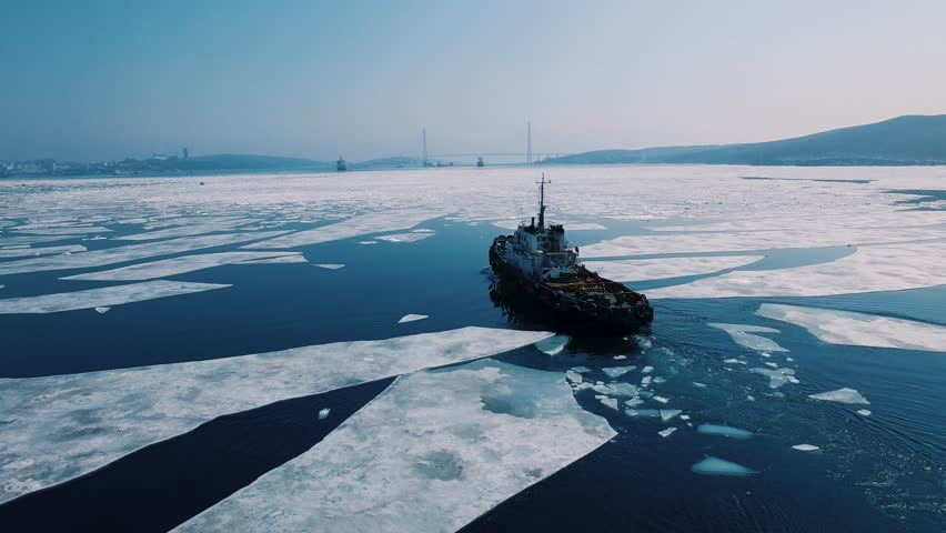 A towboat goes among the ice on the background of the city