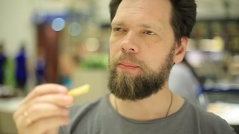 bearded man eating French fries at fast food restaurant