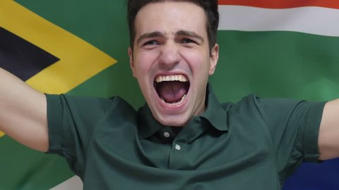 South African Young Man celebrates holding the flag of South Africa in Slow Motion