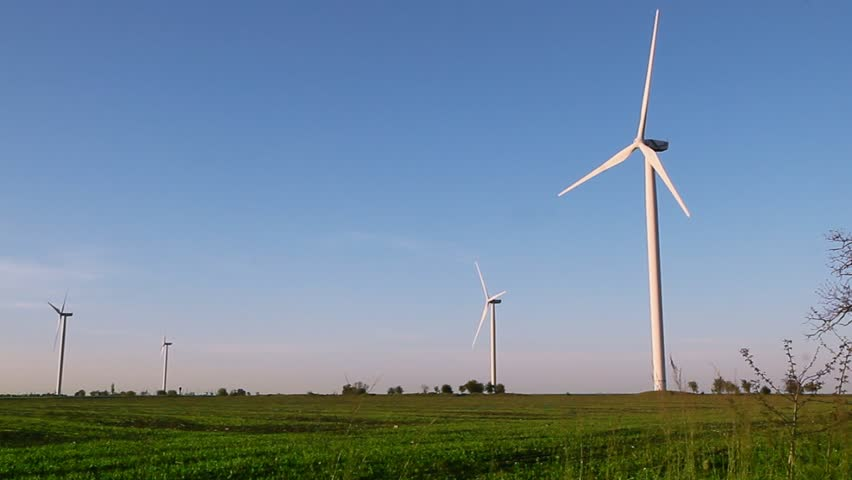 Wind energy turbines on sunset sky background, Energy generator nature friendly. Spring field.
