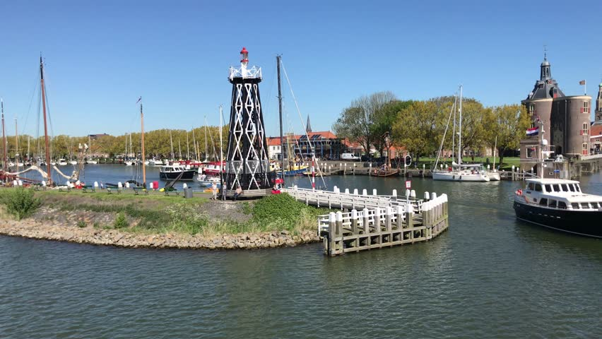 Enkhuizen, the Netherlands - May 6, 2018: Passing de harbor of the historical Dutch town of Enkhuizen. A pleasure boat exits the port of Enkhuizen.
