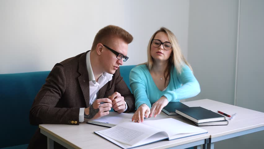 Positive male and female students doing homework together spending time in campus,colleagues making notes of creative ideas solving problems with project planning writing in notepad on meeting. | Shutterstock HD Video #1010693243