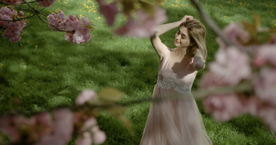 Pretty smiling blonde with natural make-up spending time in green garden. View through the blooming pink sakura tree. 4k footage.