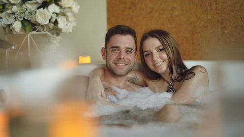 Portrait of good-looking young lovers hugging in jacuzzi, smiling and looking at camera. Burning candles, beautiful flowers and bubbling water is visible.