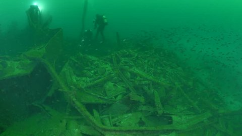 scuba divers exploring and filming world war one shipwreck underwater