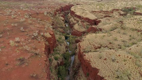Aerial view flying over canyon gorge viewing river in Karijini in the desert of Western Australia.