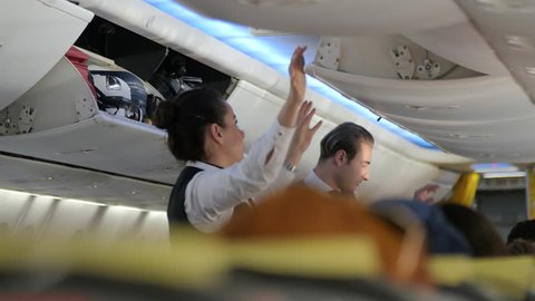 Barcelona, Spain. CIRCA November 2017: Stewardess closing the Luggage Compartment before the Flight. Flight attendant closing cabin door into overhead compartment in an airplane.