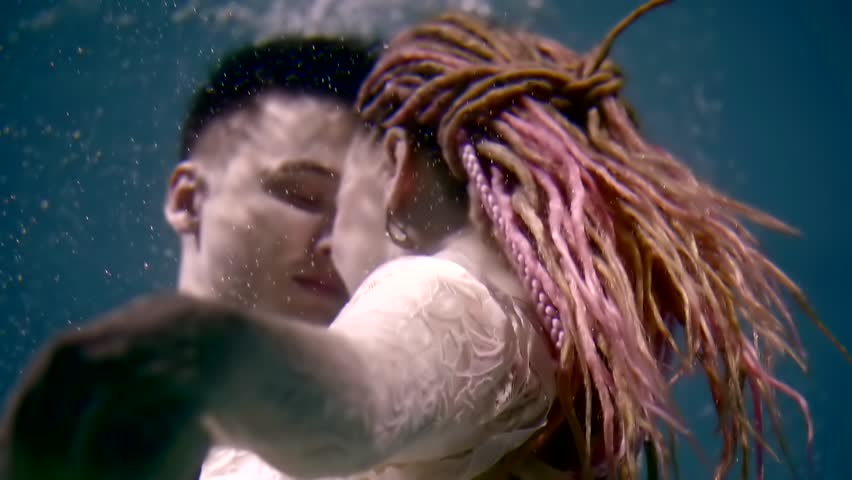 Shot from behind of an attractive woman with pink dreads kissing with a man underwater.