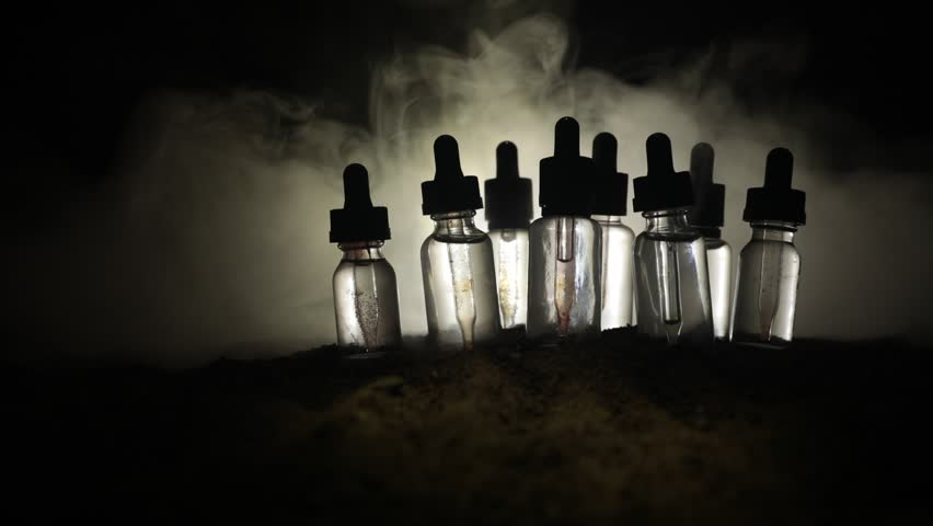 Slider shot. Vape (Electronic cigarettes) concept. Smoke clouds and vape liquid bottles on dark toned background. Light effects. Useful as background or vape advertisement. Selective focus
