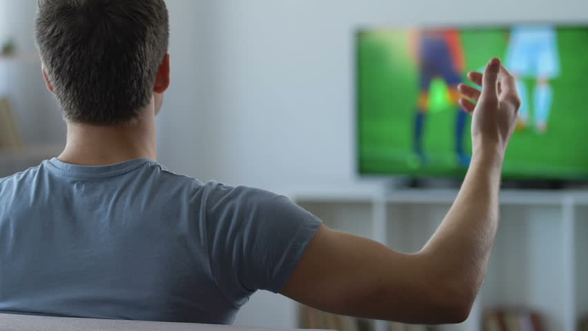Nervous man watching game on television, disappointed with result, back view