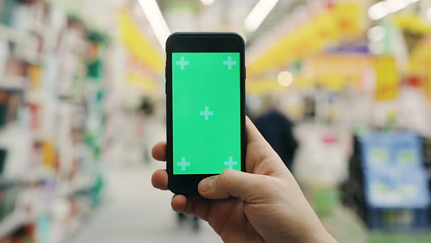 closeup shot of man hand using smartphone mobile with green screen in mall space supermarket store blur background chromakey swapping tapping touchscreen internet surfing checking price online wifi