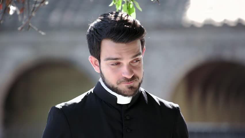 Portrait Of young Catholic Priest smiling at camera outdoor