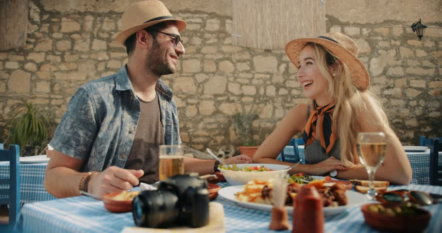 Happy couple on summer holidays in Europe having Mediterranean food at traditional restaurant | Shutterstock HD Video #1010755703