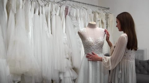 beautiful girl looking wedding dress in the cabin compared to other dresses. Preparing for the wedding. Buying a wedding dress. The seamstress inspects the finished custom made wedding dress.