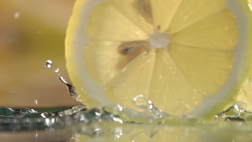 rolling lemon slices on dark background . Slow motion shot