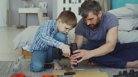 Careful father is teaching his son to work with electric screwdriver while son is trying to use screw gun and fix screw in pieces of wood. Construction and family concept.