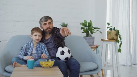 Family members father and son are watching soccer match on TV at home, cheering, celebrating victory and eating snacks. Happy family and sport concept.