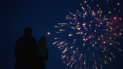 Silhouette of a loving couple of people looking at the fireworks. Guys on the background of holiday explosions look at the lights. Boy and girl hug and look at the fireworks on May 9, 2018.