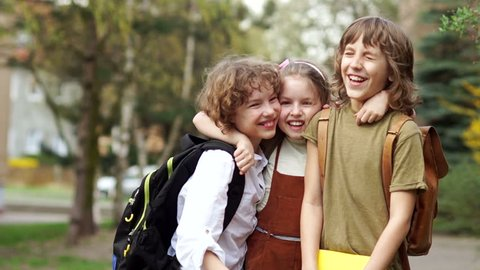 Brothers and sister cheerfully embrace each other on the way to school. Day of knowledge. Back to school. Family education