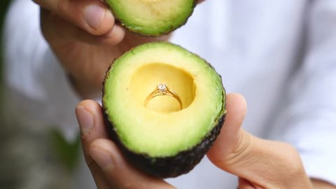 Avocado Vegan Proposal. Man Proposing With Wedding Ring In Avocado.