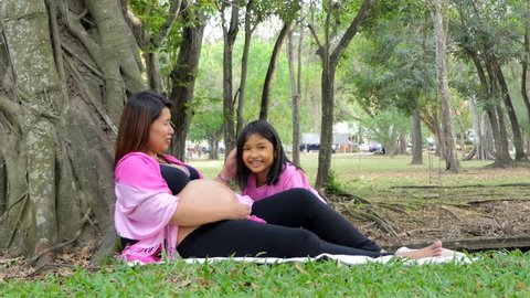 Daughter listening to pregnant mother's belly in summer day at pubic park.