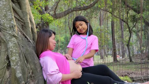 Daughter listening to pregnant mother's belly by stethoscope in summer day at pubic park.