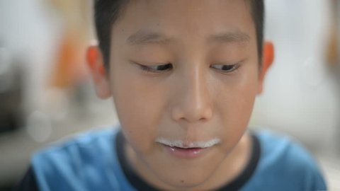 Asian boy drinking a cup of milk, milk foam on his mouth, depth of field.