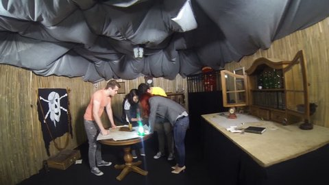 Teammates trying to open wooden puzzle box in escape room game room