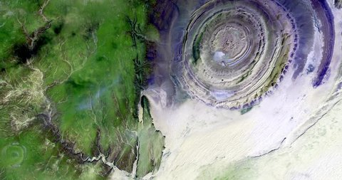 Very high-altitude overflight aerial of the Richat Structure, a geological formation in the Maur Adrar Desert, Mauritania. Clip loops and is reversible. Elements of this image furnished by NASA